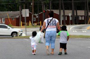 Una mujer camina con dos niños de la mano en Estados Unidos. Foto: EFE