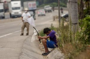 Un niño ondea una bandera blanca en la carretera pidiendo ayuda por hambre debido a la crisis economica provocada por el coronavirus, en Guatemala. EFE