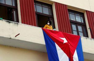 Una mujer sale al balcón donde se expone una bandera cubana, en La Habana, Cuba. EFE