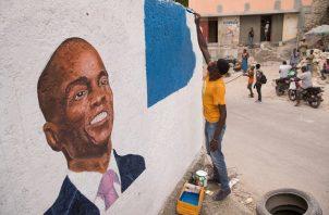 Un hombre pinta un mural en homenaje al presidente Jovenel Moise, en Puerto Príncipe, Haití. Foto: EFE