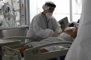 Una empleada de la salud atiende a un paciente en una unidad de cuidados intensivos para enfermos de covid-19 en el Hospital El Tunal en Bogotá (Colombia). EFE