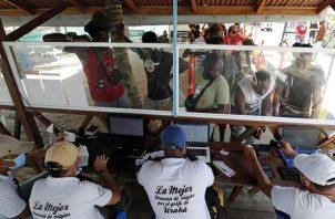 Fotografía tomada el pasado 3 de mayo en la que se registró a decenas de migrantes, de diversas partes del mundo, al comprar tiquetes para viajar a Capurganá, en el embarcadero de Necoclí (Colombia).