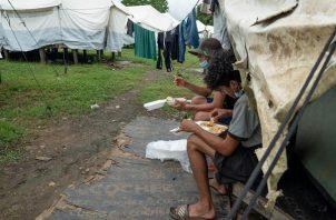 Migrantes comen en un centro de recepción en la región del Darién, selva que separa Colombia de Panamá. EFE