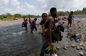 Migrantes caminan a través del río turquesa hacía la comunidad de Bajo Chiquito, tras caminar desde Colombia atravesando la selva del Darién (Panamá). Foto: EFE