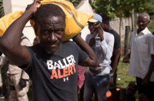 Un hombre carga ayuda humanitaria entregada por una entidad privada hoy, en las afueras de Les Cayes (Haití). Foto: EFE