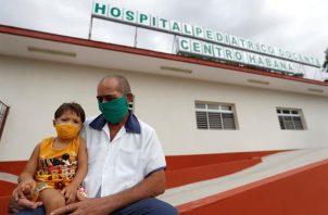 Un trabajador de la salud sostiene a un niño en sus piernas en la entrada de un hospital pediátrico hoy, en La Habana (Cuba). Foto: EFE