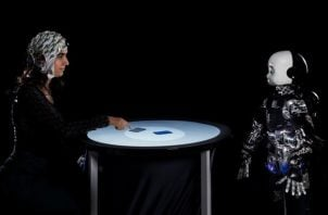 Una persona y un robot humanoide participan en un juego competitivo, mientras se mide su actividad cerebral con un electroencefalograma. Foto: EFE
