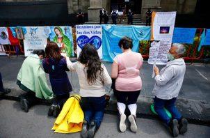 """Un grupo de mujeres en contra del aborto rezan frente a carteles de protesta """"pro-vida"""" y religiosos, afuera de la Suprema Corte de Justicia de la Nación, en la Ciudad de México. EFE"""