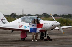 """Zara Rutherford posa con la bandera de Panamá tras aterrizar en su avión """"Shark"""" en una pista del área de carga del Aeropuerto Internacional de Tocumen. Foto: EFE"""