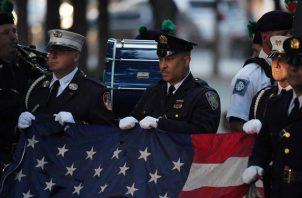 Policías y bomberos de Nueva York sostienen la bandera de Estados Unidos durante el himno nacional en una ceremonia de conmemoración de los atentados del 11S en el World Trade Center, en Nueva York (EE.UU.), este 11 de septiembre de 2021. Foto: EFE