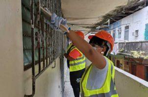 La mujer colonense está participando de la primera parte de la revitalización de los edificios, que consiste en raspar verjas y puertas de hierro para luego pintarlas.