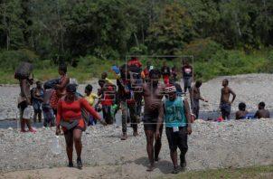 Migrantes haitianos caminan a través del río turquesa hacía la comunidad de Bajo Chiquito, en la provincia de Darién. Foto: EFE