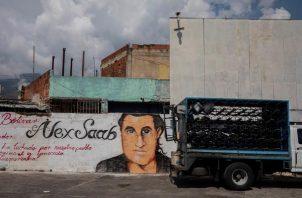 Un pequeño camión pasa junto a un grafiti con la imagen del rostro de Alex Saab en Caracas (Venezuela), en una imagen de archivo. Foto: EFE