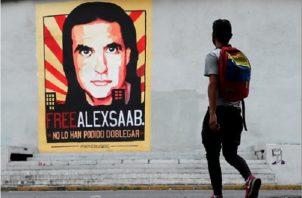 Un hombre pasa frente a un cartel de apoyo al empresario colombo-venezolano Alex Saab, en Caracas (Venezuela). Foto: EFE