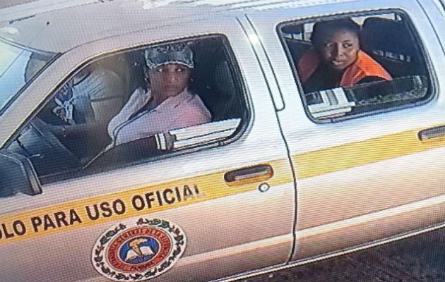 Imagen de la funcionarias vistas tomando fotos fuera de la residencia de Yanibel Ábrego.